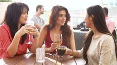Three Female Friends Enjoying Drink At Outdoor Rooftop Bar Stock Footage