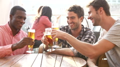 Three Male Friends Enjoying Drink At Outdoor Rooftop Bar Stock Footage