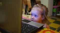 Little girl watching cartoons on laptop display at evening Stock Footage