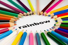 many colored pencils arranged in circle on the word rainbow - stock photo