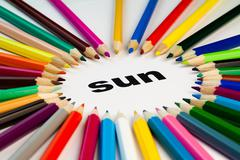 Many colored pencils arranged in circle on the word sun Stock Photos