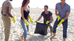 Group Of Volunteers Tidying Up Rubbish On Beach Stock Footage