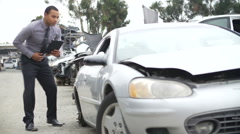 Loss Adjuster Inspecting Car Wreck Using Digital Tablet Stock Footage