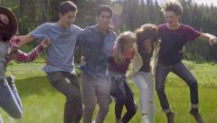 Teens Jump In The Air, And All Fall Down, Laughing (Slow Motion) Stock Footage