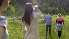 Couple Walk Through Mountain Meadow, Friends Follow Behind (Slow Motion) Stock Footage