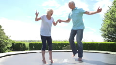 Senior Couple Bouncing On Trampoline In Slow Motion Stock Footage