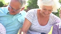 Grandparents Relaxing In Garden With Grandchildren Stock Footage