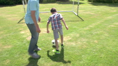 Grandfather And Grandson Playing Football In Garden At Home Stock Footage