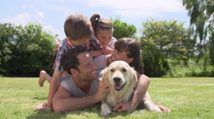Family Relaxing In Garden With Pet Dog Stock Footage