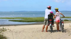 Family on a biking journey making a stop on the beach Stock Footage