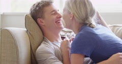 Young couple cuddling and talking on couch Stock Footage