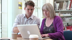 Teacher Helping Mature Student With Studies In Library Stock Footage