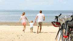 Happy family running on a sandy beach Stock Footage