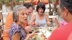 Group Of Senior Friends Enjoying Meal In Outdoor Restaurant Stock Footage