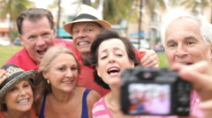 Group Of Senior Friends Taking Selfie In Park - stock footage