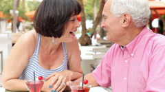 Senior Couple Enjoying Cocktails In Outdoor Bar Together Stock Footage