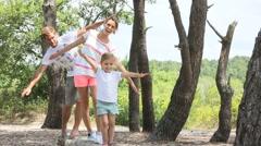 Family having fun walking on a tree trunk - stock footage