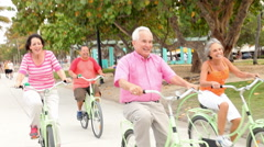 Group Of Senior Friends Having Fun On Bicycle Ride - stock footage