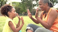 Grandmother And Granddaughter Playing In Park Together Stock Footage