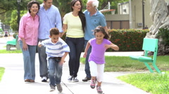 Slow Motion Shot Of Multi Generation Family Walking In Park Stock Footage