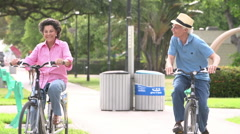 Slow Motion Sequence Of Senior Couple Riding Bikes In Park - stock footage