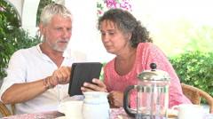Mature Couple Using Digital Tablet At Breakfast Table Stock Footage