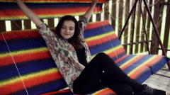 Girl relaxing on the swing and smiling to the camera Stock Footage