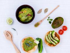 Toast with avocado creamy salad and herbs  on white table. Stock Photos