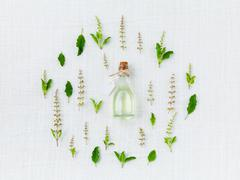 Bottle of essential oil, with holy basil leaf and flower. - stock photo