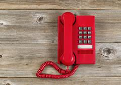 Vintage red phone on rustic wooden boards - stock photo