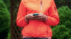 Girl typing on smartphone and putting it into pocket Stock Footage