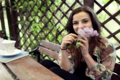 Happy girl smelling elderflower and smiling to the camera in arbour Stock Footage
