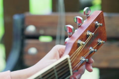 Girl touching tuning keys and tune the guitar Stock Footage
