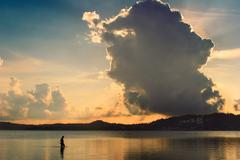 Silhouette of a fisherman in the water with dramatic sky Stock Photos