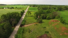Flying Over Lush Green Rural Landscape with Swollen Muddy River in Springtime. - stock footage