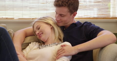 Sweet young couple smiling on couch together Stock Footage