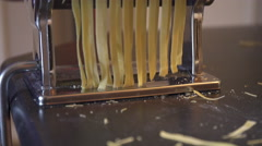 Making fresh fettuccine pasta with a traditional style pasta machine. 4K UHD. Stock Footage