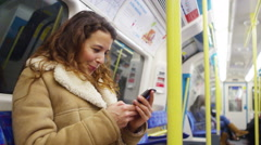 4k, young woman using her smartphone on subway underground train Stock Footage