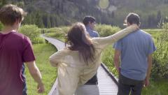 Teenage Boys Walk Along Boardwalk, Friends Catch Up (Slow Motion) Stock Footage