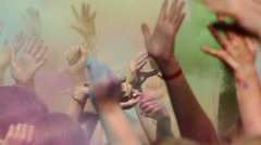 Crowd throwing hands up in air at Holi colors festival. - stock footage