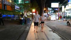 European tourist couple walk towards, night street at resort town - stock footage