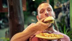 Young man eating fast food, hamburger and french fries in cafe at night HD - stock footage