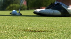 Close-up of golfer using putter to sink short putt into hole, Stock Footage