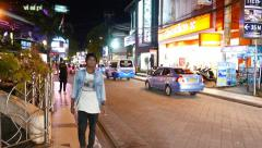 Bright illuminated night alley, glide shot, man walk towards Stock Footage
