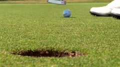 Close-up of golfer using putter to sink short putt into hole, - stock footage