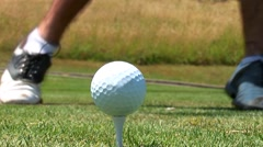 Close-up of golfer getting into stance and teeing off with driver. - stock footage
