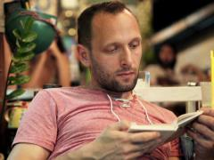 Young man reading book sitting in cafe  NTSC Stock Footage