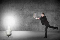 Business man run with laptop chasing light bulb Kuvituskuvat