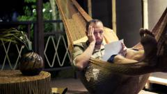 Sad, unhappy man reading bill while lying on hammock at night HD Stock Footage