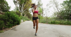 Happy Athletic Asian woman running through tunnel listening to music Stock Footage
